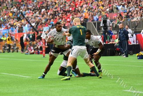 Mesulame Kunavula is stopped by the South Africa defence during their semi-final match at the Canada 7s in Vancouver yesterday. Picture: JOVESA NAISUA