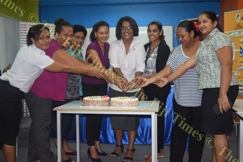 Staff members of Post Fiji, Vodafone Fiji and members of the media cut their International Women's Day celebration cake in Suva last Thursday. Picture: FILIPE NAIGULEVU