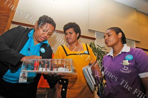 """Fijian Elections Office staff member Tarai Ligairi, left, assists Dudley High School principal Nanise Tuimanono and head girl Anna Morell during the launch of the 2018 General Election """"Know Your Election"""" awareness drive at the Grand Pacific Hotel yester"""