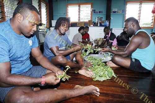 Nasoni Roko with members of the Tabadamu rugby sevens team preparing meals at their camp at Raiwai yesterday.Picture ATU RASEA