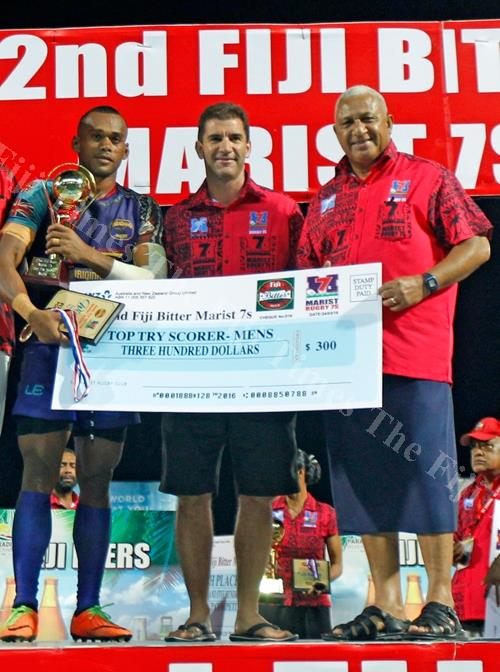 Samu Bale of Tabadamu Blue 7s team receives his Top Try Scorer prize from Prime Minister Voreqe Bainimarama and Fiji Airways Fiji 7s coach Gareth Baber during the 42nd Fiji Bitter Marist 7s tournament at the ANZ Stadium in Suva on Saturday. Picture: JONAC