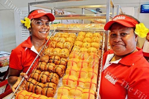 Kalesi Nakita, left, and Milianne Agnes show the variety of hot cross buns available at the Hot Bread Kitchen at Butt St in Suva yesterday. They have the normal, spice, fruit and chocolate chip hot cross buns on sale. Picture: JONA KONATACI