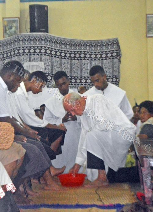 Father John Ryan washes the feet of his parishioners during the Holy Thursday mass in Labasa. Picture: SERAFINA SILAITOGA