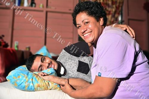Maleli Saladrau finds comfort in his mother's arms as he recovers at his home in Suva after being in a coma for three weeks at the ICU ward in CWM Hospital. Maleli survived a near fatal accident last month after he was hit by a bus. Picture: JOVESA NAIS