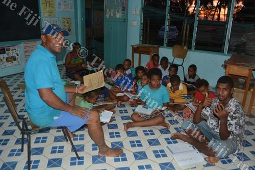 Pastor Leone Naivalubasaga helps the children with their studies at the Deshbandhu Primary School Evacuation Centre in Lautoka. Picture: REINAL CHAND