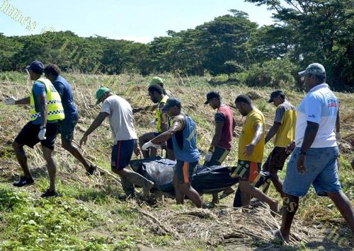 Police officers and Sabeto villagers carry the body of Ilaisa Nabou out of the Naboutini river in Sabeto, Nadi yesterday. Picture: BALJEET SINGH