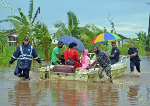 Police officers ferry a grandmother and her granddaughter in a boat in Vulovi, Labasa yesterday. Picture: LUKE RAWALAI