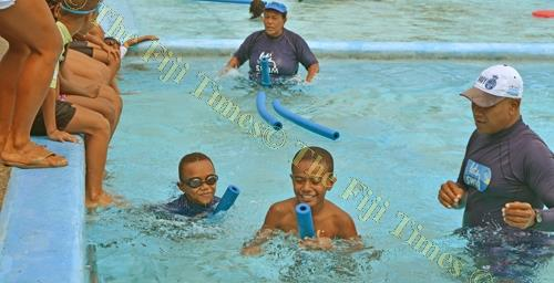 Swimming instructors help children during their 'Let's swim program at the Suva Olympic Pool yesterday. Picture: PAULINI RATULAILAI