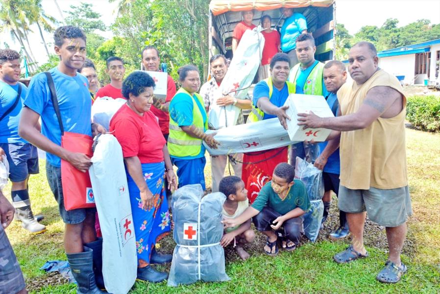 Nasolo Village representative Etuate Naqora (right) receives gifts from Red Cross officials. Picture: REINAL CHAND