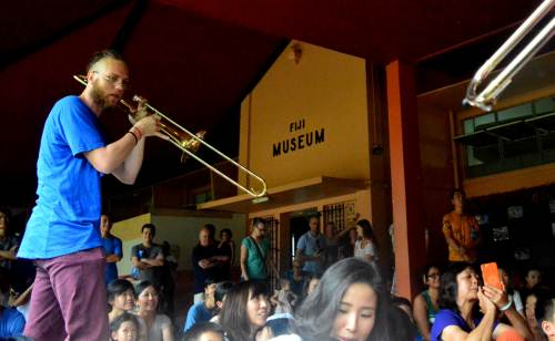 Lionel Zink of Globeshakers Project Brass Band performing at the Fiji Museum this afternoon as the public watch on. Picture: JONA KONATACI