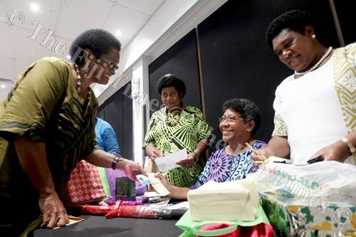 Left, Sala Naucabalavu receives Taina Leweniqila's contributon during the Methodist Women's Fellowship fundraising dinner at Holiday Inn Suva on Friday. Picture: JOVESA NAISUA
