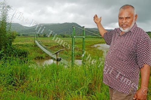 Mohammed Munaf Khan points at the slumped Nakorotari hanging bridge which has been closed to public. Picture: LUKE RAWALAI