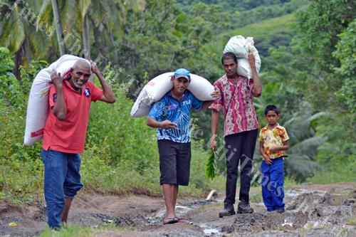 Residents walk along the Valebasoga feeder road with sacks. They claim because of the poor road conditions, they have to walk for about an hour to reach their homes. Picture: LUKE RAWALAI