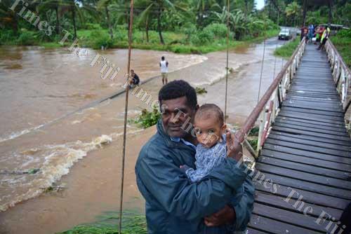 Mikaele Qeretabua with his granddaughter Tamanaisi Ilaitia looks over the flooded Qauia bridge in Lami yesterday. Picture: JOVESA NAISUA
