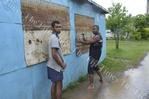 Joape Sova, right, with his son Navitalai Ratudina put up the shutters at their home at Taiperia settlement in Lautoka. Picture: REINAL CHAND