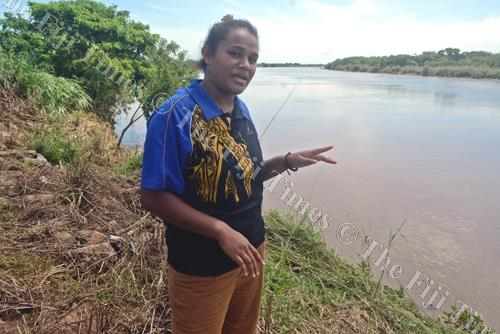 Asinate Waqa shows the spot from where she saw a body floating in the Ba River on Tuesday afternoon. Picture: REINAL CHAND