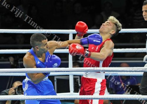 Fiji's Winston Hill, right, connects with a left on his Scottish opponent Stephen Newns in their quarter-final boxing match. The Fijian slayer out-boxed the Scotsman for a semi-final spot. Picture: ELIKI NUKUTABU