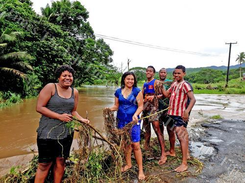 Youths of Bulileka, Labasa clear debris piled on a bridge brought by the flood. Picture: LUISA QIOLEVU