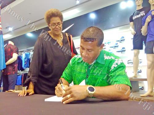 Former Fiji 7s coach Waisale Serevi signs an autograph during his book launch in Suva yesterday. Picture: PAULINI RATULAILAI