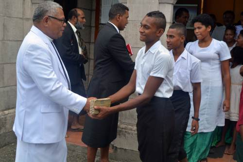 Gau Secondary School athletes shake hands with Reverend Dr Mosese Salusalu after their church service at the Centenary Methodist Church in Suva today. Photo: PAULINI RATULAILAI