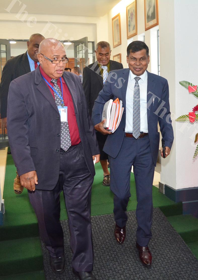 Opposition MP's Semesa Karavaki and Biman Prasad leave parliament during a break in the sitting yesterday. Picture: JOVESA NAISUA
