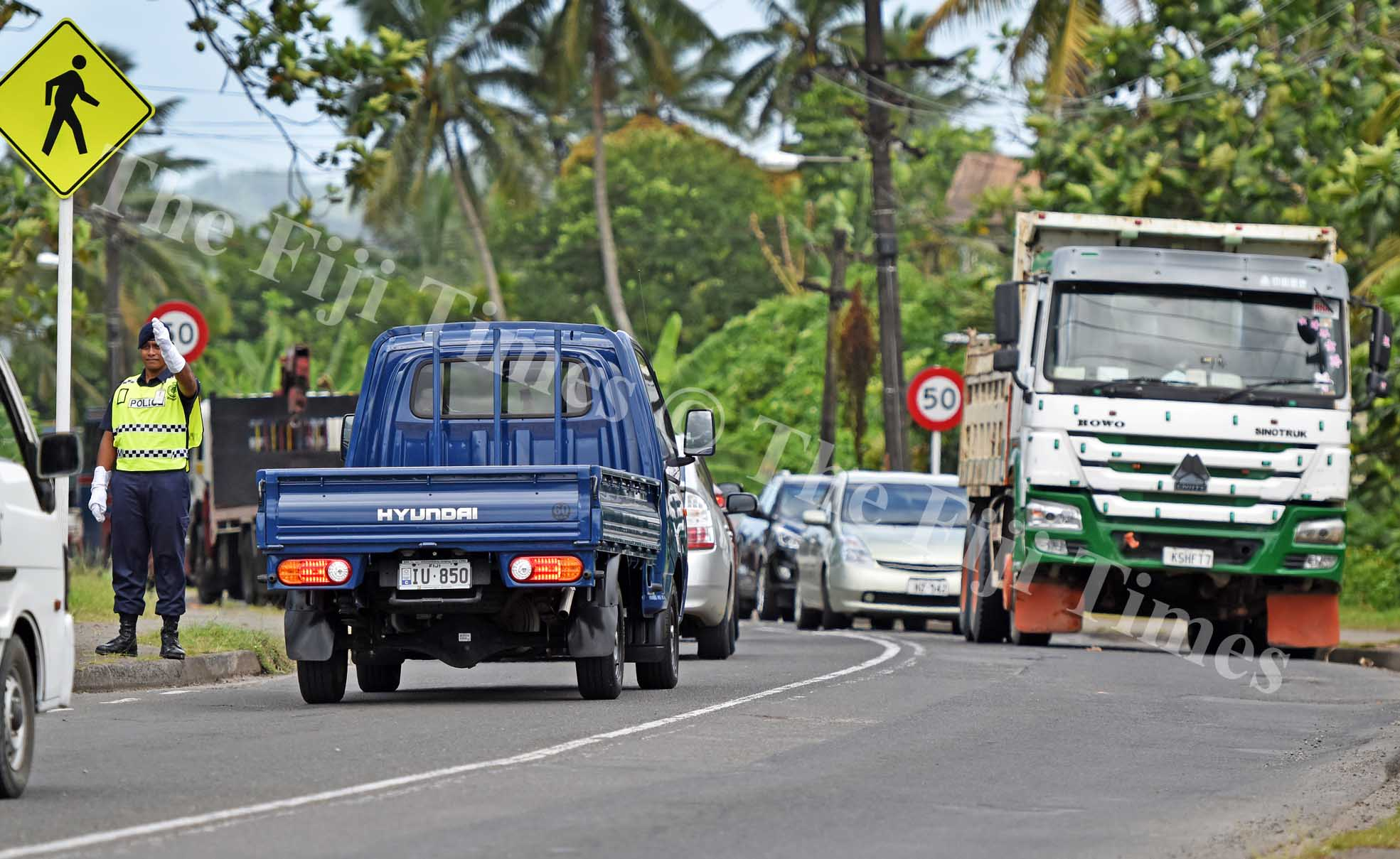 A police officer directs the traffic jam along Queens road near Lami town during a truck (on right) broke down near Lami Village in Lami yesterday. Picture: RAMA