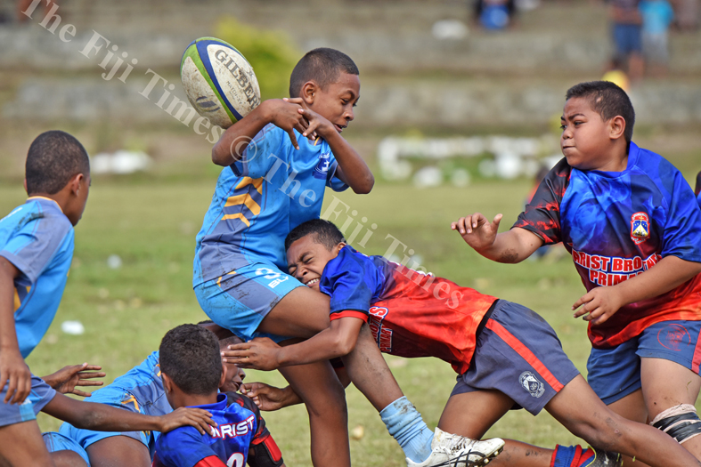 Ronald Tom of John Wesley Primary School losses the ball in a tackle from the Marist Suva Street primary during the Suva Kaji rugby at Gospel grounds yesterday. Picture: RAMA