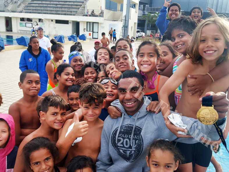 Fiji swimmer Epeli Rabua holds up his gold medal amidst yoiung swimmers at the National Aquatic Centre in Suva yesterday. Picture: ELIKI NUKUTABU
