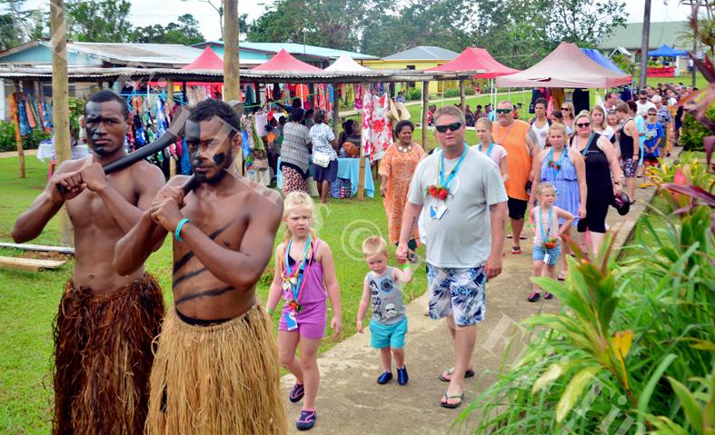 Traditonal warriors Jone Navuso and Uraia Rokoli escort tourist from the cruiseliner Carnival Legend at Coloisuva village yesterday. Picture: JONA KONATACI
