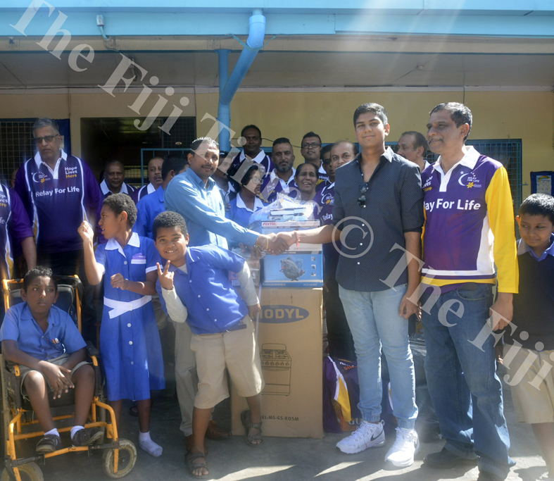 (R-L) Raben Singh and son Shiv Bhan Sngh, 15, hand over the donated items to Lautoka School for Special Education assistant head teacher Kailash Pillay in Lautoka yesterday. Picture: REPEKA NASIKO