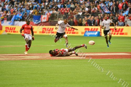 Fly like a Fijian ... Alasio Naduva keeps his eye on the ball as he chases a kick from Amenoni Nasilasila inside the Fiji Airways Fiji 7s team 10-metre line after a Kenyan player loses possession during the cup final match at the Canada 7s in Vancouver ye