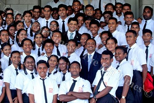 Students of Vunimono High School join MPs Aiyaz Sayed-Khaiyum and Vijay Nath for a photo session outside Parliament yesterday. Picture: JONA KONATACI