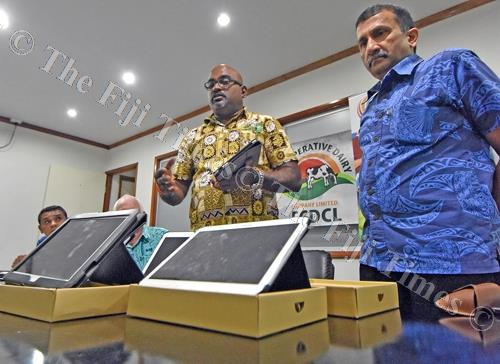 FCDCL chief executive officer Sachida Nand (left) receives the IPad from deputy program manager Krishnan Narasimhan of Pacific Financial Inclusion Programme in Nausori yesterday. Picture: RAMA