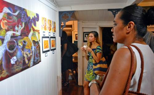 Guests take a look at artworks on display during the art exhibition in Suva on Thursday night. Picture: JONACANI LALAKOBAU