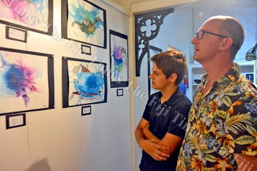 Matt Young, closest to camera, and Graham Ovenden Young view artwork on display during the art exhibition in Suva on Thursday. Picture: JONACANI LALAKOBAU