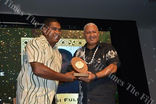 Saiasi Fuli receives his prize for being the best coach for 2017 from Prime Minister Voreqe Bainimarama on Friday night. Picture: BALJEET SINGH