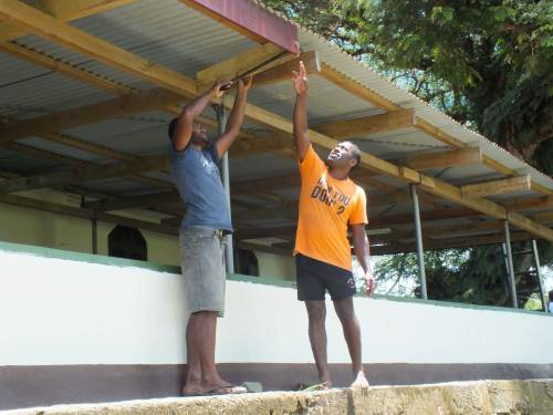 Matamaivere villagers help prepare the church roof for the new guttering. Picture: SUPPLIED