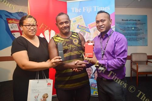 Huawei Technologies Fiji retail dealer executive Sam Rabuku (right) presents Marika Banuve (centre) with his brand new Huawei phone joined by Annie Robinson, marketing manager for The Fiji Times. Picture: JOVESA NAISUA
