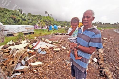 Apenisa Malai, 68, carries his grandson Joeli Tiko at Nasau Village on Koro. Picture: JONA KONATACI
