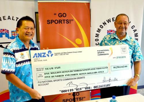 Team Fiji deputy chef de mission Christopher Yee, left, receives the cheque from Fiji National Sports Commission chairperson Peter Mazey during a press conference at the FASANOC office in Suva this morning. Picture: JONACANI LALAKOBAU