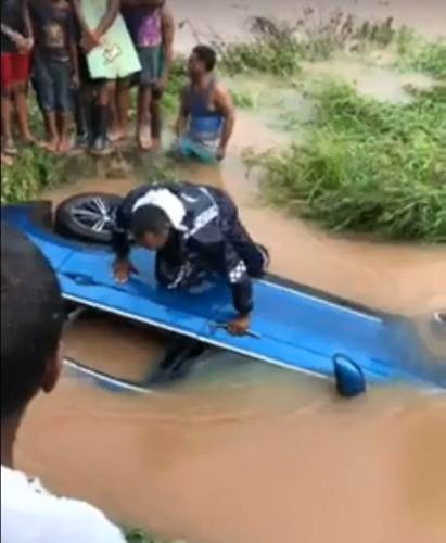 Police inspect a vehicle caught in the floods in Lautoka. Picture: screen grab from video by SHIRI RAM