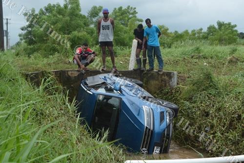 Lovu residents look at a car stuck in a drain after be swept away by strong currents due to flooding in Lautoka. Picture: REINAL CHAND