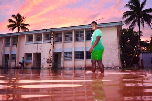 Manasa Ravulolo treads across flooded waters outside the old Navua Sub-divisional hospital on Sunday evening. Picture: JOVESA NAISUA