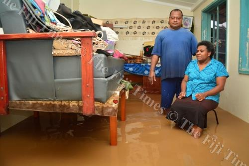 Ward sister at the Navua Hospital Maternity Unit Selai Camaibau with her husband inside their home filled with flood waters in Navua on Sunday evening. Picture: JOVESA NAISUA