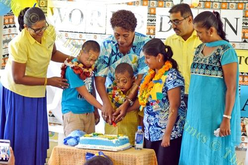 Disability Welfare Officer North Niumai Marama and students of cut the celebratory cake during the event. Picture: LUKE RAWALAI