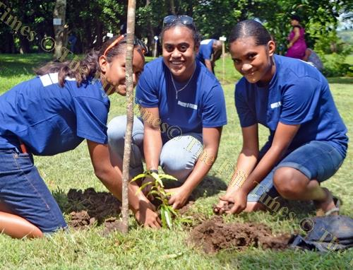 Friends, from left, Sonya Alfred, Nancy Thaggard and Ulita Alfred plant a tree during the celebrations. Picture: LUKE RAWALAI