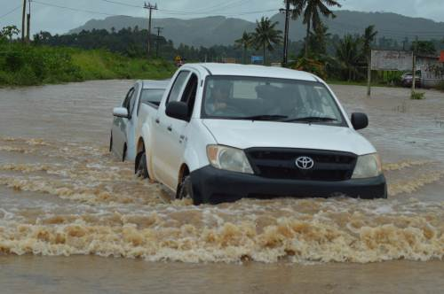 Two vehicles struggle across flood waters at the Vulovi Road this morning. Picture: Luke Rawalai