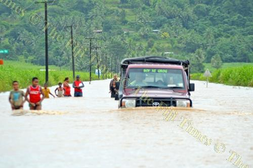 A vehicle tries to cross floodwaters in Vunivau outside Labasa yesterday. Picture: LUKE RAWALAI