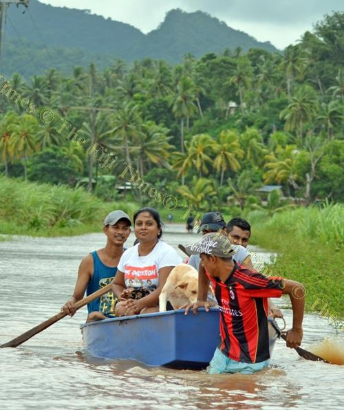 This family traversed Vunivau in Labasa in a boat with their pet dog yesterday. Picture: LUKE RAWALAI