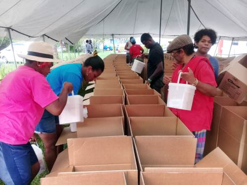 Volunteers packing food into the box at the Vodafone head office in Tamavua for flood victims in the West. Picture ATU RASEA
